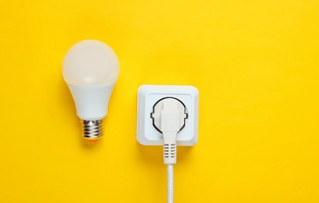 Cavo bianco inserito nella presa di corrente e lampadina a led. vista dall'alto