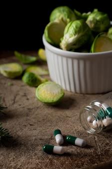 Cavoletti di bruxelles del primo piano sulla tavola con le pillole