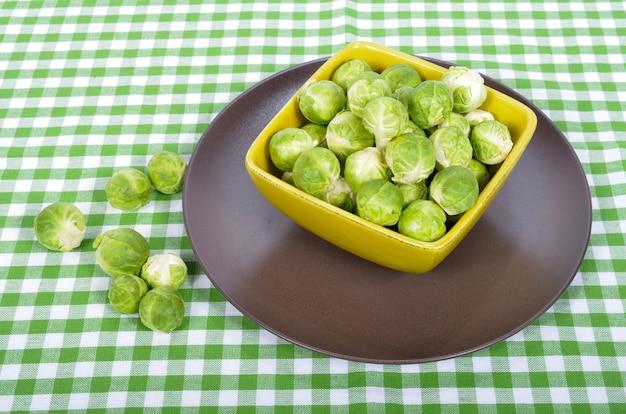 Cavoletti di bruxelles in un piatto marrone sull'asciugamano verde