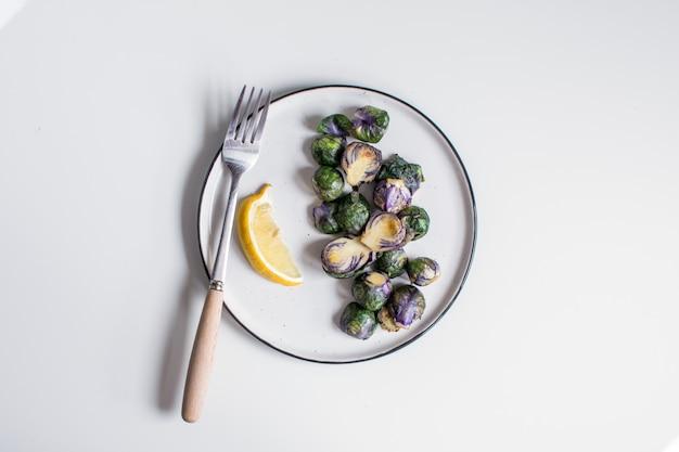 Cavoletti di bruxelles viola fritti sul piatto con limone