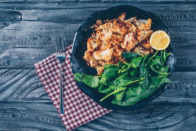 Cavolfiore fritto in un piatto con la vista superiore di verdi su un panno di picnic e su un fondo di legno scuro