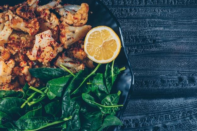 Cavolfiore fritto vista dall'alto nel piatto con verdure e limone su fondo di legno scuro. orizzontale