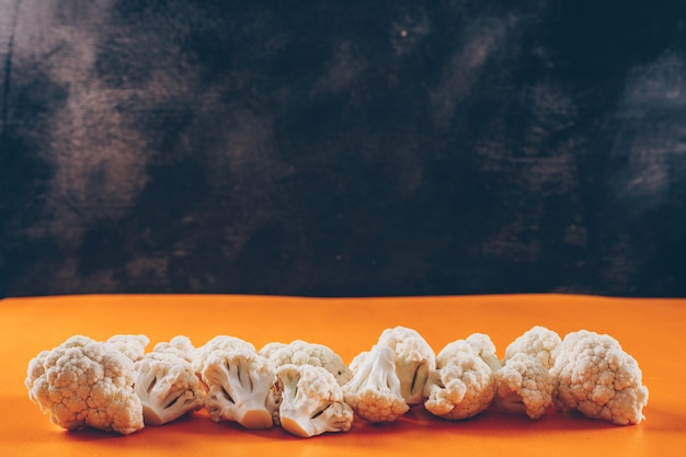 Cavolfiore su uno sfondo arancione e scuro. vista laterale. spazio per il testo