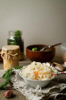 Cavolo fermentato, cetrioli su fondo di legno. immagine verticale