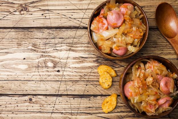 Cavolo stufato con salsicce in ciotole di legno sul tavolo. messa a fuoco selettiva