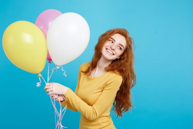 Celebrando concetto - close up ritratto felice giovane bella ragazza attraente redhair sorridente con palloncino partito colorato. sfondo blu pastello.