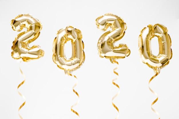 Celebrazione del nuovo anno 2020. palloncini in lamina d'oro numero 2020 appesi in aria su sfondo bianco