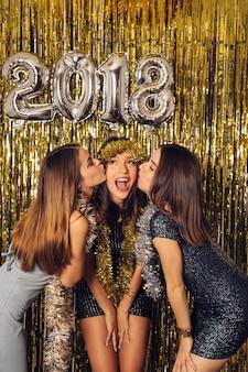 Celebrazione del nuovo anno con le ragazze baciare amico