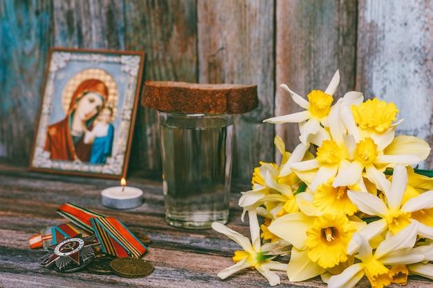 Celebrazione delle medaglie del giorno della vittoria, icona ortodossa e una candela accesa, un mazzo di fiori di narciso e un bicchiere di vodka con un pezzo di pane di segale sul tavolo