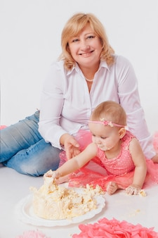 Celebrazione di compleanno: bambina che mangia dolce con le sue mani su bianco. il bambino è coperto di cibo. dolcezza rovinata.