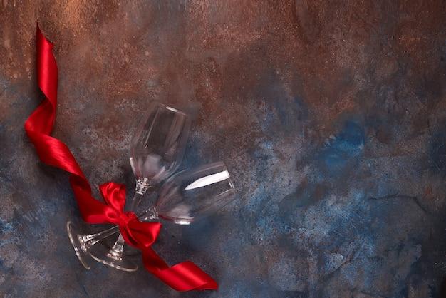 Celebrazione di giorno di san valentino con due bicchieri e nastro rosso su sfondo di pietra
