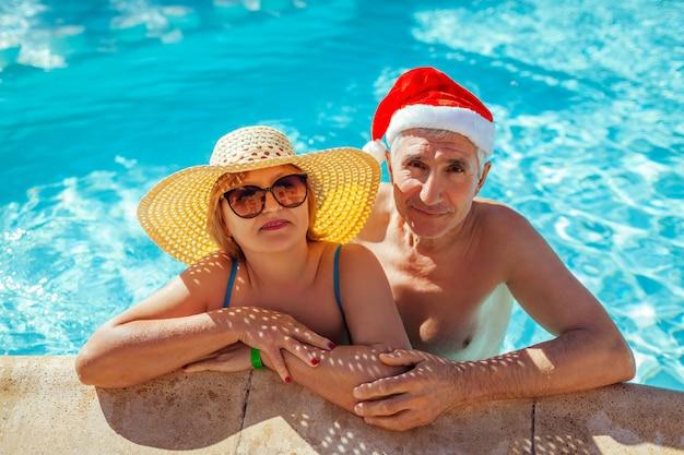 Celebrazione di natale e capodanno. uomo in cappello e donna di santa che si rilassano nella piscina. vacanza tropicale