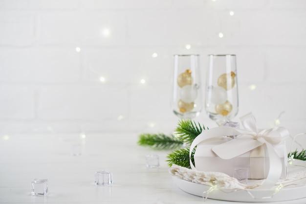 Celebrazione di nuovo anno tavola di natale in argento con due bicchieri di champagne sul tavolo da pranzo e confezione regalo. con le stelle filanti