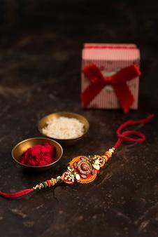 Celebrazione di raksha bandhan con un elegante rakhi, chicchi di riso, kumkum e confezione regalo. un tradizionale cinturino da polso indiano che è un simbolo di amore tra fratelli e sorelle.