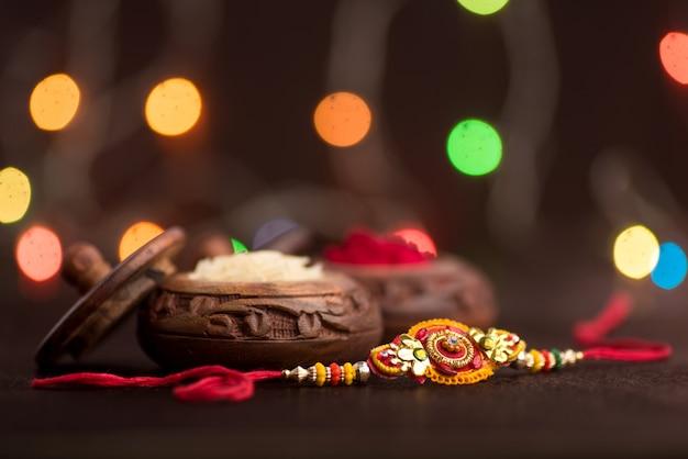 Celebrazione di raksha bandhan con un elegante rakhi, rice grains e kumkum. un tradizionale cinturino da polso indiano che è un simbolo di amore tra fratelli e sorelle.
