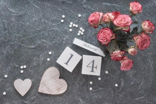 Celebrazione di san valentino, piatto disteso con calendario in legno, rose rosa e cuori in legno su oscurità