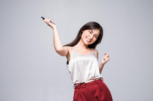 Celebrazione estatica felice di successo della donna asiatica di successo vincente isolata sulla vita bianca della parete in su.