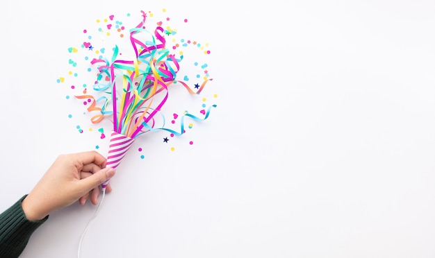 Celebrazione festa e anniversario con la mano della donna che tiene coriandoli colorati