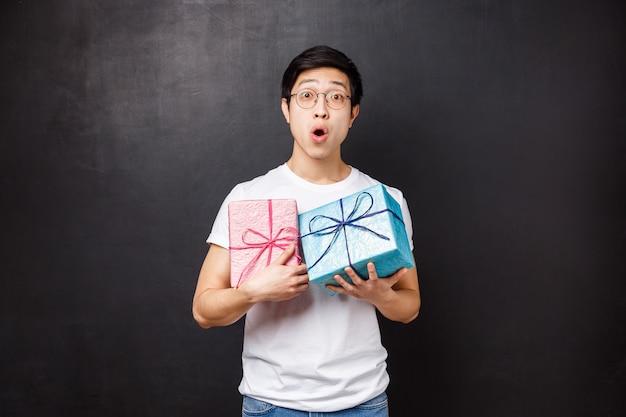 Celebrazione, vacanze e concetto di lifestyle. il ritratto del giovane felice emozionante sorpreso che celebra il compleanno, riceve i regali di b-day, tenendo due contenitori di regalo e sembra colpito la macchina fotografica