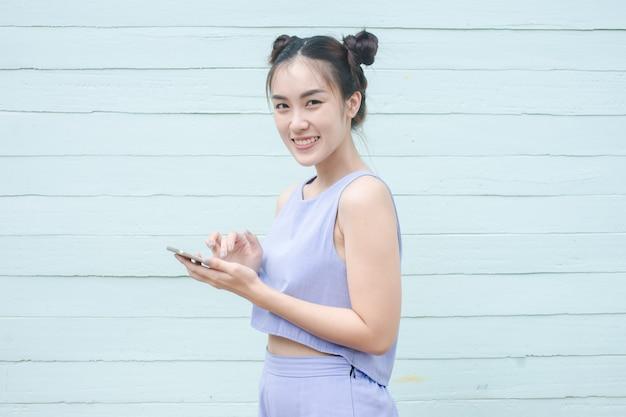 Cellulare asiatico di uso della donna di bellezza isolato su fondo