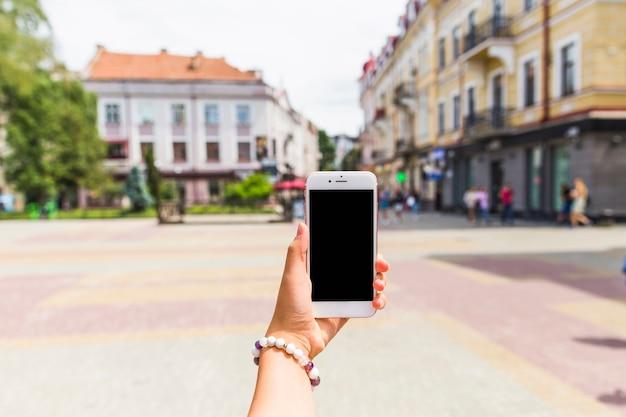 Cellulare della tenuta della mano della donna con lo schermo in bianco a all'aperto
