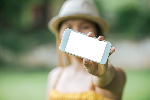 Cellulare della tenuta della mano della donna, smartphone con lo schermo bianco