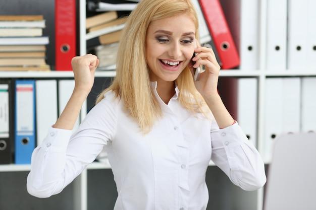 Cellulare sorridente biondo bello di conversazione della donna di affari