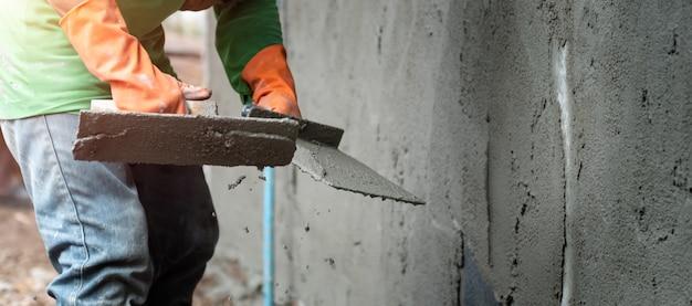 Cemento intonacante del lavoratore manuale del primo piano sulla parete per la costruzione della casa