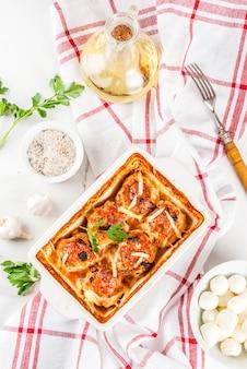 Cena di dieta sana fatta in casa, polpette di tacchino di pollo preparate con salsa, formaggio, verdure. su un tavolo di marmo bianco, con spezie.