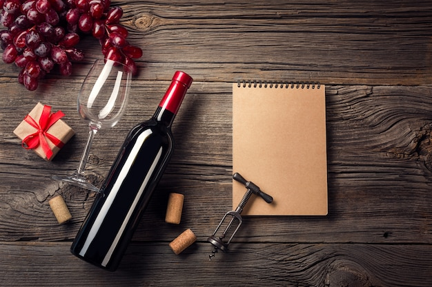 Cena di festa con vino rosso e regalo su legno rustico in vista piatta laica.
