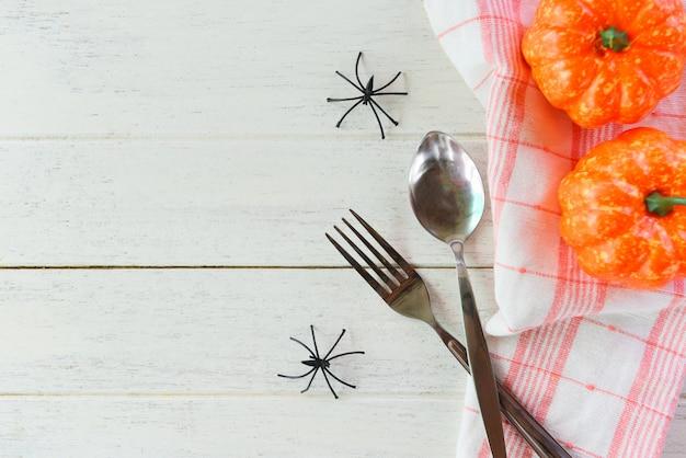 Cena di festa degli accessori della decorazione della regolazione della tavola di halloween con la forchetta e la zucca del cucchiaio del ragno sulla tovaglia nei precedenti di legno bianchi