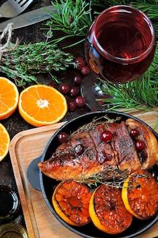 Cena di natale. petto di pollo al forno con mandarini e mirtilli rossi. rami di albero di natale e un bicchiere di vino.