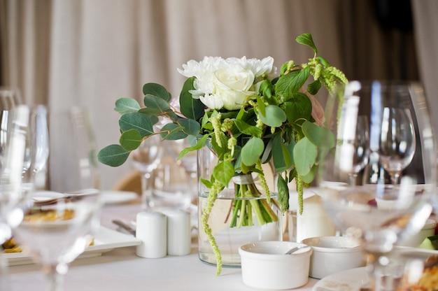 Cena di nozze nel ristorante, tavoli decorati con vasi di rose.