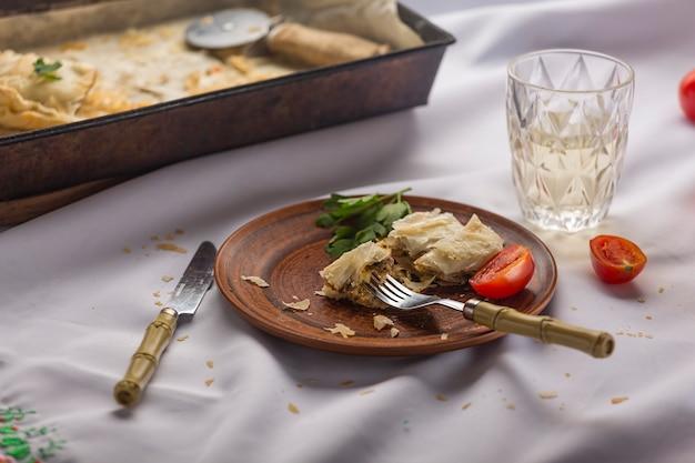 Cena fatta in casa. natale, ringraziamento. torta di carne e vino su un tavolo con una tovaglia bianca