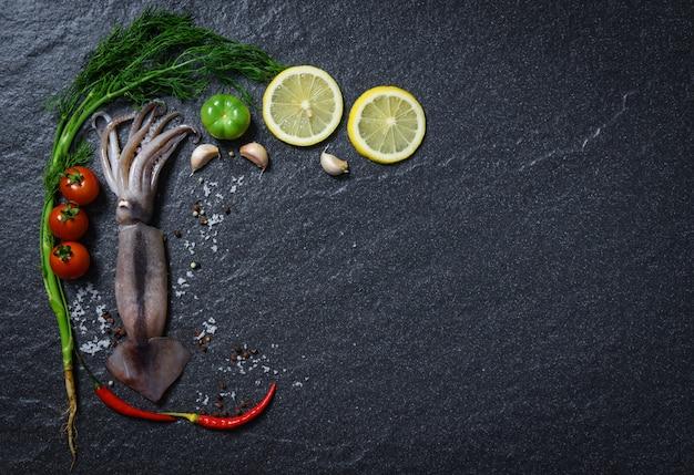 Cena gourmet di pesce fresco calamari crudo oceano con erbe e spezie con pomodoro limone