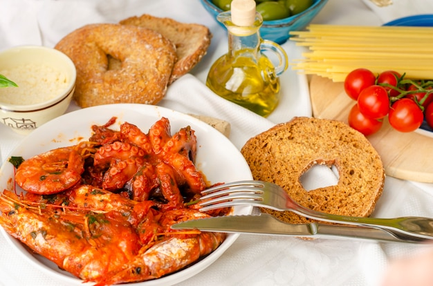 Cena gustosa per gli amanti del pesce. gamberi e polpo in salsa di pomodoro. concetto di cibo italiano.