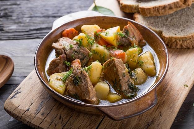Cena irlandese. la carne di manzo ha stufato con le patate, le carote e il pane della soda sulla tavola di legno, la vista superiore, spazio della copia. comfort invernale fatto in casa, cotto lentamente