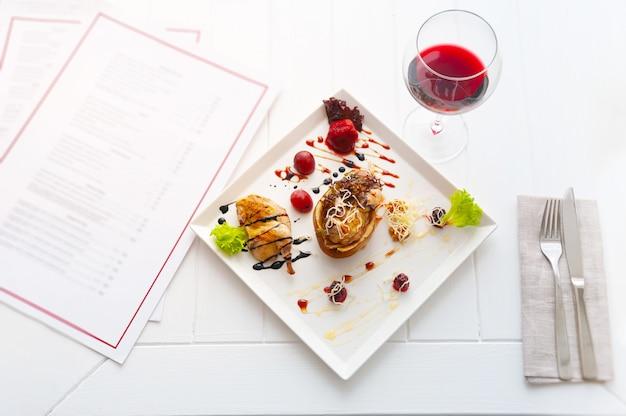 Cena o pranzo con piatto per una persona. interno bianco di lusso del ristorante. vino rosso e pollo con pera