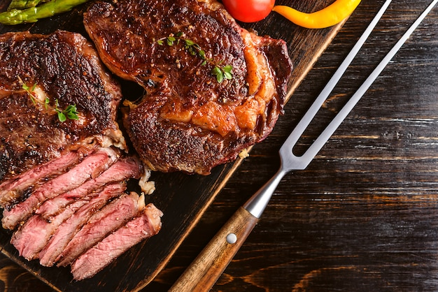 Cena per due deliziose bistecche succose, asparagi con parmigiano e verdure.