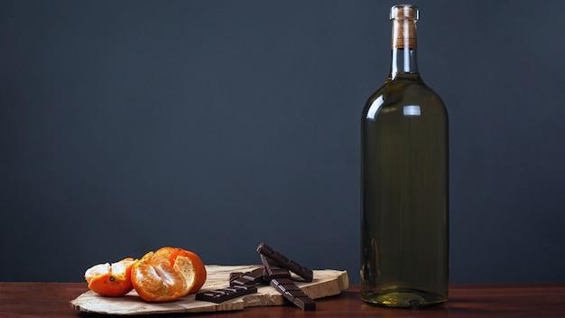 Cena romantica. bottiglia di vino con dolci cioccolatini e mandarini su uno sfondo scuro.