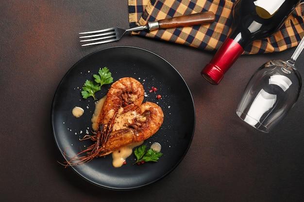 Cena romantica con gamberetti a forma di cuore e vino su uno sfondo marrone. vista dall'alto con lo spazio della copia