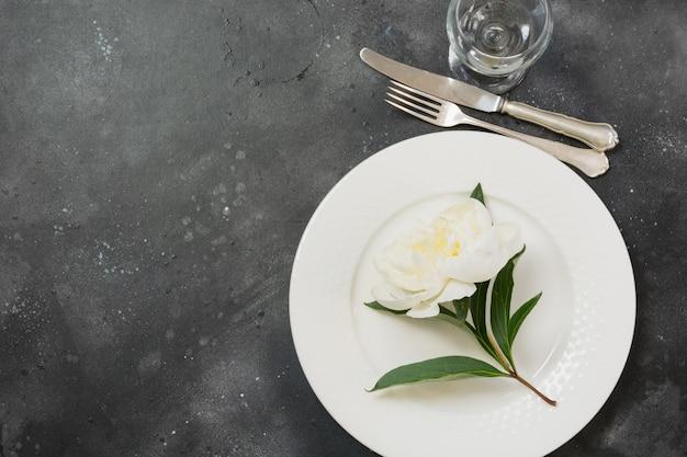 Cena romantica. regolazione della tabella con la peonia bianca sulla tabella nera. vista dall'alto con spazio di copia.