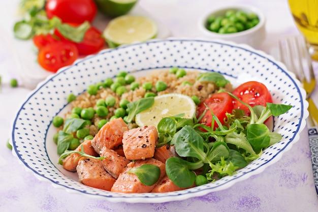 Cena salutare. fette di salmone grigliato, quinoa, piselli, pomodoro, foglie di lime e lattuga