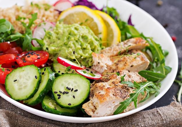 Cena salutare. pranzo a base di buddha con pollo grigliato e quinoa, pomodoro, guacamole, cavolo rosso, cetriolo e rucola.