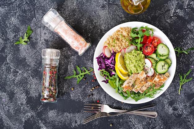 Cena salutare. pranzo della ciotola di buddha con pollo arrostito e quinoa, pomodoro, guacamole, cavolo rosso, cetriolo e rucola sulla tavola grigia. disteso. vista dall'alto