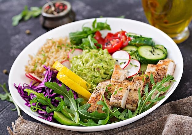 Cena salutare. pranzo della ciotola di buddha con pollo arrostito e quinoa, pomodoro, guacamole, cavolo rosso, cetriolo e rucola sulla tavola grigia.