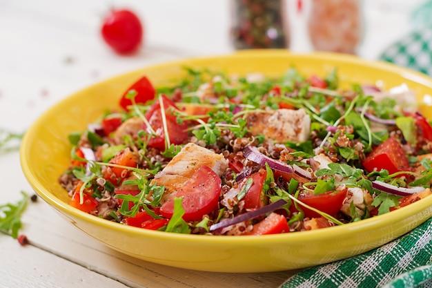 Cena salutare. pranzo insalatiera con pollo grigliato e quinoa, pomodoro, peperoni, cipolle rosse e rucola