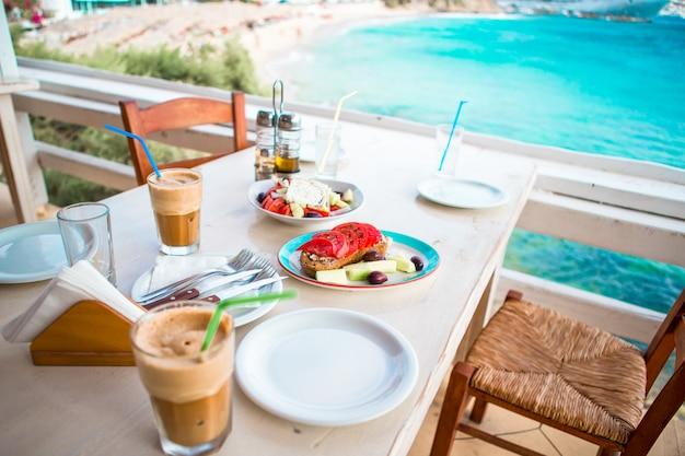 Cena tradizionale con deliziosa insalata greca fresca, frappe e brusketa servita a pranzo nel ristorante all'aperto con splendida vista sul mare e sul porto