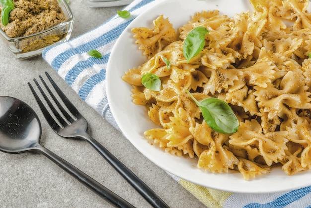 Cena vegana. pasta di farfalle con salsa di pesto e foglie del basilico sul fondo di pietra grigio del piatto bianco