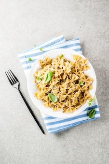 Cena vegana. pasta di farfalle con salsa di pesto e foglie del basilico sul piatto bianco, superficie grigia della pietra, spazio della copia